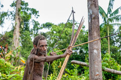 Papuan shooting from a bow. Royalty Free Stock Photos