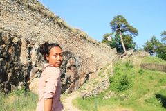 Serious girl walking on castle Girls Stone. Papuan tourist girl - serious young woman on path by wall on castle Girls Stone, Czech Republic Royalty Free Stock Photography