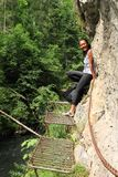 Tourist on Canyon Breakthrough in Slovak Paradise. Papuan tourist - young smiling woman standing on iron steps and holding chain while leaning on rock on path in royalty free stock photos