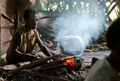 Papuan woman cooks food. Royalty Free Stock Photography