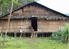 Papuanen lurar framme av traditionellt hus Arkivfoto