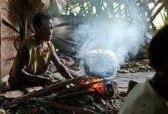 Papuanfrau kocht Lebensmittel. Lizenzfreie Stockfotografie