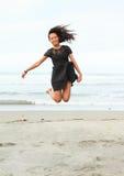 Papuanmeisje die op strand springen Stock Afbeeldingen