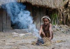 Papuanpojke som gör brand, Wamena, Papua, Indonesien royaltyfri foto