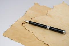 Papyrus und schwarzer Stift auf grauem Hintergrund lizenzfreie stockfotos
