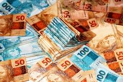 Paquet brésilien d'argent avec 10 et 100 notes de reais Photo libre de droits