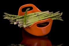 Paquet d'asperge sur un plat de portion orange Image libre de droits