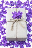 Paquet de boîte-cadeau enveloppé avec le papier et la corde avec les fleurs pourpres Images libres de droits