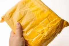 Paquet de colis ou boîte jaune de cargaison avec le produit dans la main masculine, l'expédition logistique gratuite et la distri photo stock