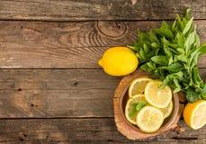 Paquet de menthe et tranches de citron sur le vieux fond en bois cop Photos libres de droits