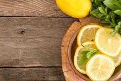 Paquet de menthe et tranches de citron sur le vieux fond en bois cop Images libres de droits