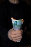 Paquet de roubles brûlants dans la main de person's image stock