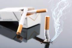 Paquet et bout de cigarette sur le gris Photos libres de droits