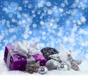 Paquet pourpre de Noël, cadeau d'un ruban argenté Les tintements du carillon, les boules argentées de Noël et le Noël tient le pr Photographie stock