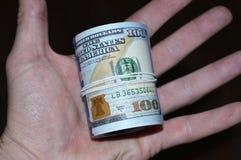 Paquet tordu de 100 billets d'un dollar à disposition Image stock