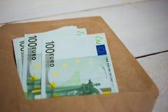 paquete ascendente cercano de billetes de banco de los euros del dinero en sobre en la tabla de madera foto de archivo