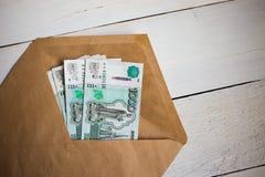 paquete ascendente cercano de billetes de banco rusos del dinero mil rublos en sobre en la tabla de madera imagen de archivo libre de regalías