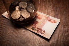 Paquete de billetes de banco y un tarro de cristal con las monedas Imagen de archivo