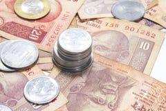 Paquete de billetes indios y de monedas de la moneda que mienten en la tabla Foto de archivo