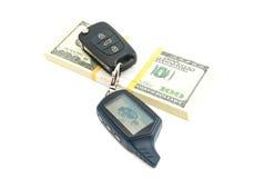 Paquete de cientos dólares de billetes de banco y llaves del coche Imagen de archivo