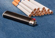 Paquete de cigarrillos y del encendedor en tejanos con bolsillos foto de archivo