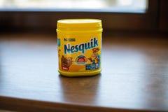 Paquete de la bebida Nesquik del chocolate y del cacao por Nestle en el fondo de madera fotografía de archivo
