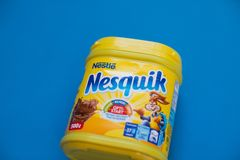 Paquete de la bebida Nesquik del chocolate y del cacao por Nestle en fondo azul foto de archivo libre de regalías