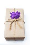 Paquete de la caja de regalo envuelto con el papel y la cuerda con las flores púrpuras Imágenes de archivo libres de regalías