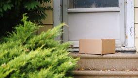 Paquete de la entrega en el pórtico de la casa El hombre está poniendo la caja cerca de la puerta Salida a la puerta almacen de metraje de vídeo