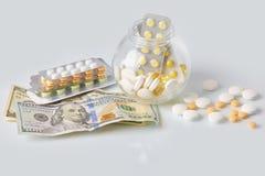 Paquete de las píldoras de la medicina con tres paquetes de monedas y de la botella de cristal con el dinero del efectivo del dól foto de archivo libre de regalías