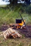 Paquete de leña en un fondo de una hoguera con el pote Fotos de archivo libres de regalías