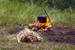 Paquete de leña en un fondo del fuego con un pote Foto de archivo libre de regalías