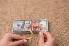 Paquete del billete de banco de dólar de EE. UU. atado con una cinta Fotografía de archivo libre de regalías