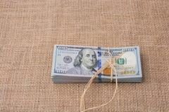 Paquete del billete de banco de dólar de EE. UU. atado con una cinta de lino Imagen de archivo