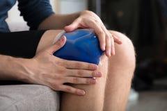 Paquete del gel de Person Sitting And Applying Ice en rodilla imagen de archivo libre de regalías