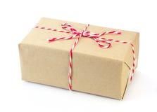 Paquete del papel de Brown atado con la secuencia roja y blanca Fotos de archivo libres de regalías