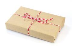 Paquete del papel de Brown atado con la secuencia roja y blanca Fotografía de archivo libre de regalías