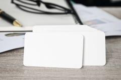 Paquete en blanco de la tarjeta de visita de la identidad corporativa en la tabla del trabajador con la trayectoria de recortes e Imagen de archivo