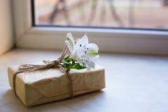 Paquete envuelto con la sola flor del alstroemeria cerca de la ventana Fotografía de archivo libre de regalías