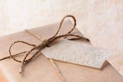Paquete envuelto en papel de Brown con la etiqueta del regalo Imágenes de archivo libres de regalías
