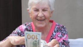 Paquete feliz de la tenencia de la abuela de dinero en manos y la dispersi?n de moneda extranjera en el escritorio Retrato de la  almacen de metraje de vídeo