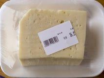 Paquete hecho de la película de estiramiento con el número blanco del queso y del código de barras marcada con etiqueta por el me foto de archivo