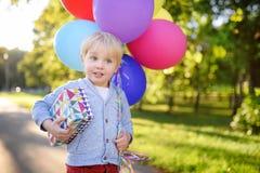Paquete lindo de la tenencia del muchacho de globos y de regalo coloridos en una caja festiva ¡Feliz cumpleaños! Imagenes de archivo