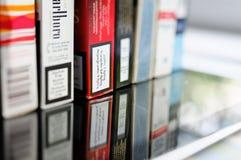 Paquete múltiple de los cigarrillos en la tabla de cristal Fotos de archivo