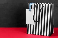 Paquete para las compras en una tira con un precio en una tabla roja en un fondo negro con un lugar para una inscripción Concepto fotografía de archivo libre de regalías
