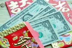Paquete rojo chino con las notas del dólar de EE. UU. Imágenes de archivo libres de regalías