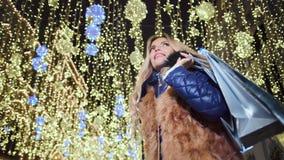 Paquete sonriente de la tenencia de la mujer del comprador del ángulo bajo con el regalo en el fondo brillante del bokeh de las l metrajes