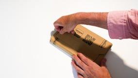 Paquete unboxing de la cartulina del Amazon Prime de la mano del hombre metrajes