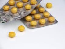 Paquetes abiertos de píldoras amarillas en la tabla blanca imagenes de archivo