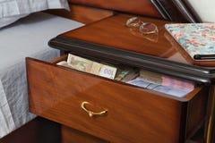 Paquetes de billetes de banco en mesita de noche Foto de archivo libre de regalías